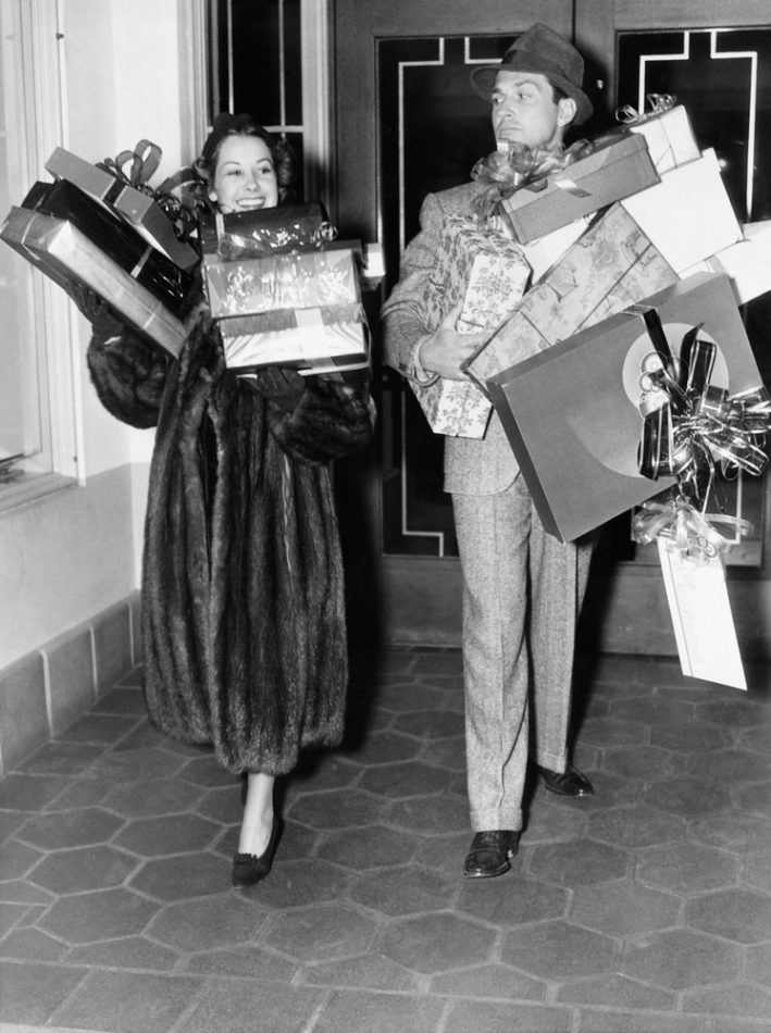 vintage couple walking holding stacks of presents -- loot, contests, giveaways, travel tech gear clothing
